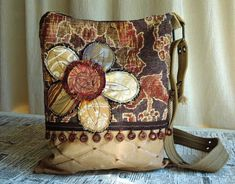 This CROSSBODY HOBO BAG is done in earthy warm tones...just in time for Autumn! The beaded wood trim adds to the nature inspired look and the scrappy flower adds a nice whimsical touch. Perfect for both the young and the young at heart! NOTABLE DETAILS: Two repurposed cotton belts work in tandem to create an adjustable strap with a nice soft texture and is comfortable to wear across the body, keeping your hands free, or simply wear it over the shoulder. The inside is completely lined with a…