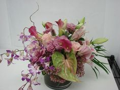 This is a floral arrangement that features lilies, anthurium, miniature calla lilies and dendrobium orchids in a pale pink and green color scheme.  See our entire selection at www.starflor.com.  To purchase any of our floral selections, as gifts or décor, please call us at 800.520.8999 or visit our e-commerce portal at www.Starbrightnyc.com. This composition of flowers is generally available for same day delivery in New York City (NYC).  LV024