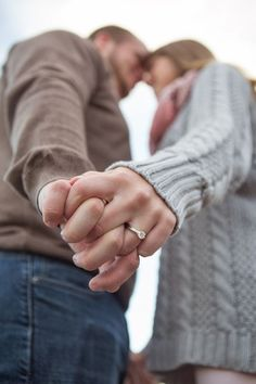 The camera angle is set in such a way to make sure the ring stands out in this unique engagement picture. #Camera #Angle #HoldingHands #Engagement #Focus #Ring #Love #Blurred