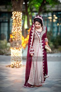 How crazy unique is this bride's dress? It seems like a maroonish red combined with a pale tea pink, amazing! Pakistani Couture, Pakistani Wedding Dresses, Pakistani Outfits, Indian Outfits, Pakistani Gharara, Indian Dresses, Desi Wedding Dresses, Asian Wedding Dress, Bridal Outfits