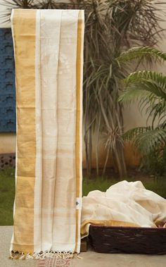 A subtle off-white khadi silk dazzles with a goldenborder. The palluhas an elegant and distinguishing gold and silver floral work that livens the sari.