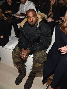 Kanye West was bundled up in the front row at Ralph Lauren, rocking a pair of camo pants with some combat boots.