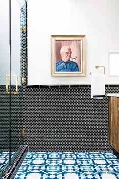 A quirky bathroom that has combined a black penny round tile with a mosaic blue-and-white floor tile