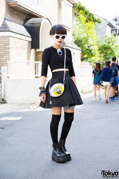 15-year-old Moeka on the street in Harajuku wearing an all black look with a cropped sweater, Hellcatpunks skirt, as well as Demonia boots and other accessories from Never Mind the XU Harajuku.