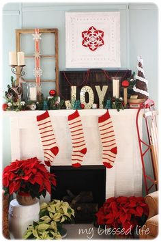 Mix wreath, open frame with ornaments hanging Christmas wall decor on wall above mantel. Stockings, lit garland candles below. Mrs in vase with ornaments hanging from branches if needed for balance.