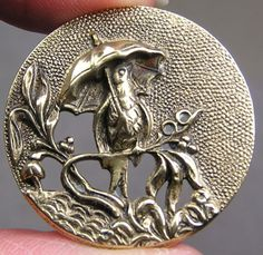 Bird under umbrella, brass button.  Love the detailing on this one.  For sale on ebay.