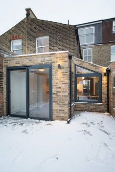 This smart extension combines old and new. Dark framed glass doors and windows give a contemporary look. The design doesn't attempt to blend in with the older part of the property, but become a complimentary addition, adding space and light to the house.