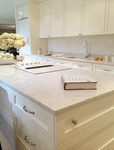 The elegant, monochromatic design emphasizes an extensive island topped with marble-like Cambria Torquay Cambria Torquay, Cambria Countertops, Outdoor Kitchen Countertops, Kitchen Counters, White Quartz Countertops, Countertop Options, Kitchen Cabinets, Kitchen Slab, New Kitchen