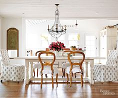 In order to accommodate their family of eight, homeowners custom-built a dining table based on a model they loved. Shabby chic Rachel Ashwell chairs, a serious steal found on social media, cozy up to the table. Neutral slipcovered Parsons chairs break up the set while maintaining the room's airy vibe.