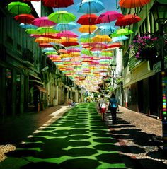 Photographer Patrícia Almeida captured this colorful umbrella installation along a sidewalk in Águeda, Portugal