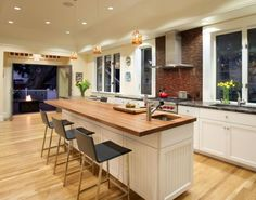 modern kitchen with wooden island and hardwood flooring