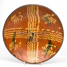 """PENNSYLVANIA SLIP-DECORATED EARTHENWARE / REDWARE CHARGER,lead-glazed, semi-deep form with coggled rim, center with strong yellow-slipped decoration and copper splashes. Second half 18th century. 2 3/4"""" H, 13 1/4"""" D."""