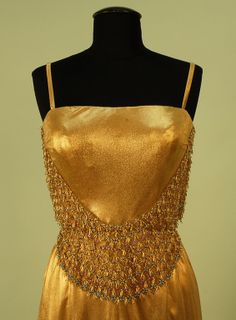 "GOLD LUREX and BEADED METALLIC LACE EVENING GOWN, 1960's. Boned bodice with narrow strap, a wide U-shaped band of metallic lace beaded in pink, blue, gold and pearls applied below breast continues around bodice back, slightly trained skirt pleated in back for fullness, bodice closes with hooks & eyes, skirt snaps over zippered lining. Label ""Veneziani Milano"". Front Detail"