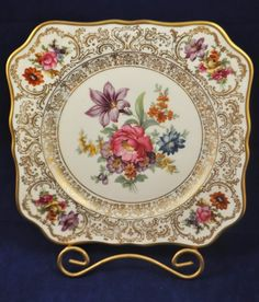 spectacular set of (6), 1970s floral square ornate gilt hand painted desert plates, finished by the legendary Carl Schumann Dresden decorating studio. Schumann continued to hand decorate fine German china in the classic Dresden style for well over 100 years, and our set of plates feature brilliant center spring floral sprays, copious gilding, and 4 beautiful corner floral medallions. The bases carry the 1970s vintage (post Arzberg) Dresdner Art China Schumann Made in Bavaria gold stamp in…