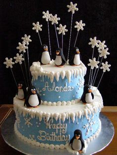Birthday cake with fondant penguins and snowflakes on wires.