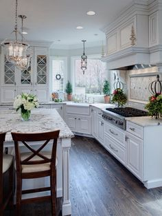 20 Ways to Decorate With Flowers For Spring - gorgeous, clean white kitchen with elegant drop lighting, a marble island and white flowers