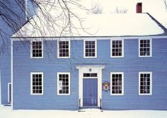 A bright blue colonial house is a stunning contrast against crisp white snow