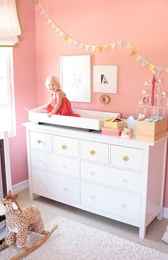 i like the pink walls and the banner running on the wall. in other news i swear that little girl is like 5 and doesn't need to be on a changing table. (cute though)