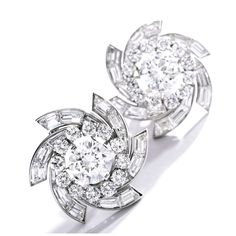 Pair of Platinum and Diamond Earclips, Van Cleef & Arpels Centering two round diamonds weighing 3.52 and 3.29 carats, within swirled mounts set with baguette diamonds weighing approximately 6.50 carats, accented by round diamonds weighing approximately 4.30 carats, signed Van Cleef & Arpels, numbered 15029.