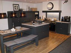 Landelijke grijze keuken met warme parket als vloer. Deze keuken is redelijk donker door de keuze van de keukenkast, maar in combinatie met het hout krijgt deze keuken een warm gevoel.