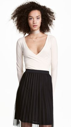 1f2531a1da Long-sleeved bodysuit in jersey. Low-cut front neckline with attached  wrapover. Snap fasteners at gusset.