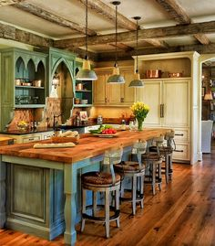 A rustic country kitchen with a color palette of dusky blue and ivory. The natural pine floors match the butcher block countertop of the kitchen island, which has four barstools with wicker seats. Exposed wooden beams criss-cross the ceiling of this kitchen. Above one of the cabinets, copper pots are displayed. The deep arches of the cabinets above and to the left and right of the stove add a touch of elegance.