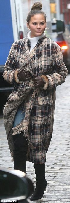 New York chic: The 31-year-old had wrapped herself in a navy, beige, white and scarlet tartan jacket with heavy fringe running down its middle