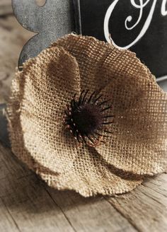I REALLY THINK THIS IS GREAT. MAKE A PATTERN FOR THE PETALS- USE A BLACK BUTTON AND SEW IT ON TO TWO PIECES OF BURLAP THAT IS TWICE THE SIZE OF THE BUTTON. FRAY THE EDGES OF THE CIRCLE OF BURLAP AND SEW TO MIDDLE OF FLOWER