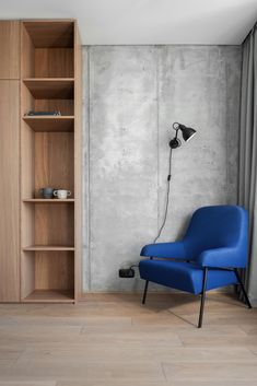 A modern home office with long curtains, a blue armchair, wood shelving, and a concrete wall.