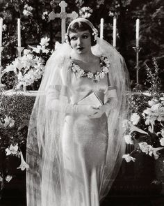 Sleek and sexy and yet sweet and romantic, socialite Ellie Andrews (Claudette Colbert) captured the look of an ethereal bride in this flower-trimmed silk, body-conscious gown by costume designer Robert Kalloch for the 1934 drama. Movie Wedding Dresses, Wedding Dress Costume, Wedding Movies, Wedding Scene, Wedding Night, Wedding Gowns, Wedding Bells, Wedding Stuff, Dream Wedding
