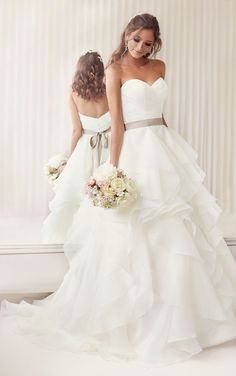 Elegant gown with a figure-flattering asymmetrical ruched bodice, and soft, billowing layers of ivory organza throughout its A-Line skirt and chapel train. Matching with ribbon sash.