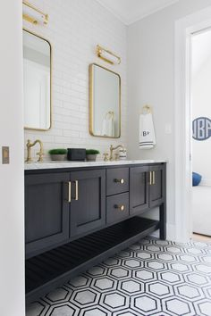 Black and gray marble floor tiles lead to a black wooden dual bath vanity boasti. Black and gray marble floor tiles lead to a black wooden dual bath vanity boasting a slatted shelf and a white marble countertop holding antique brass. Bathroom Floor Tiles, Bathroom Wallpaper, Boy Bathroom, Tile Floor, White Bathroom Tiles, Marble Bathrooms, 2nd Floor, Wall Tiles, Modern Bathroom