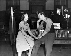 Medium BTS shot of Judy Garland as Mary Holden rehearsing a scene on the library set with director Busby Berkeley.