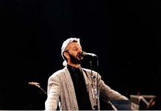 Starr performing for the Prince's Trust, Wembley Stadium, England, 6 June 1987.  Starr in his forties, wearing a grey jacket and a black shirt, standing behind a microphone and singing.