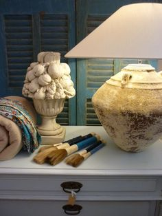 Lichtblauwe ladenkast, oude louvreluiken, kaligrafeerkwasten, grote lampvoet.