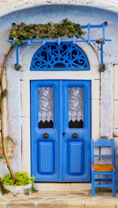 The beautiful blue doors of Oia, Santorini, Greece. Can we build an awning for our Virginia creeper, for shade, at the front door?