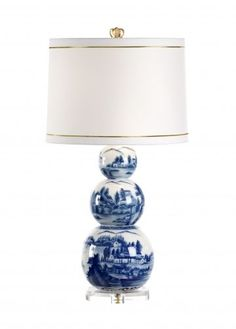 """This lovely table lamp is made with porcelain and features a scenic design in blue and white. The lamp has an acrylic base and comes with a white shade with gold accents. The lamp measures 26""""H and th"""