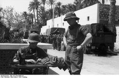 Afrika Korps soldier gets a uniform patched up with sewing machine, Libya 1941.