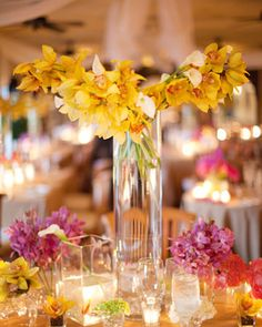 Bunches of sunny-hued flowers artfully arranged in tall vases