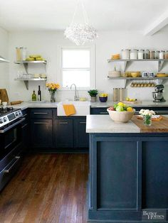 Deep, inky blue adds a note of drama to this 1950s farmhouse-style kitchen, and it stands in contrast to the white walls and countertops. A funky chandelier and open metal shelving infuse this composed space with contemporary flair.