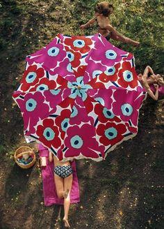 Women partially sunbathe beneath an Unikko print umbrella by Finnish firm Marimekko, United States, photograph by Tony Vaccaro.