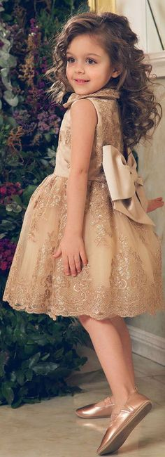 Gorgeous baby girls dress, perfect for weddings, Eid and other celebrations this Spring Summer. For baby girls, I love this special occasion dress by Junona, made in beautiful lace with shimmery floral embroidery. It has an adorable, large satin bow on the back and layers of tulle on the inside skirt. Looks perfect with these girls special occasion gold leather ballerina pump shoes from David Charles. #kidsfashion #babydress #eid #girlsdresses #childrensclothing #girlsclothes #girlsclothing