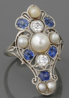 An Art Deco cultured pearl, sapphire, diamond and platinum shield ring