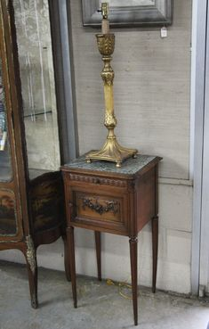 """2 PIECE MISCELLANEOUS LOT CONSISTING OF A LOUIS XVI STYLE CARVED WALNUT CHEVET HAVING GREENISH GRAY MOLDED MARBLE TOP OVER 1 DRAWER AND 1 MARBLE LINED CUPBOARD DOOR RESTING ON TAPERD REEDED CARVED LEGS; ALONG WITH A GOLD GILT CARVED WOOD PRICKET CANDLESTICKS LAMP;  34""""H X 17""""W X 15""""D CHEVET"""