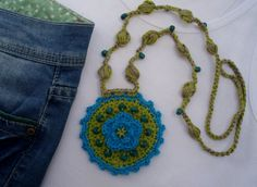 Locket necklace with turquoise and green with central flower and wooden beads. Cord tissue also crochet with beads.  Medallion Diameter: 8 cm. ¨ cord length: 80 cms.  The weight is very light.