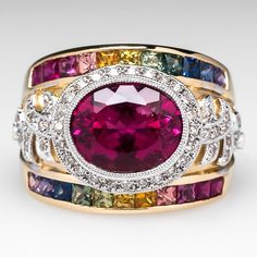 This wide band rubellite tourmaline cocktail ring is centered with a white gold bezel set natural rubellite gemstone. The shoulders of the ring are accented with diamonds set into migrained white gold. Channel set into two rows are alternating rainbow sapphire accents. This ring is crafted of solid 18k two-tone gold.