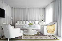 Salón de una de las habitaciones/bungalow junto a la piscina del hotel Delano. Interiorismo blanco nuclear con alfombras en tonos verdes