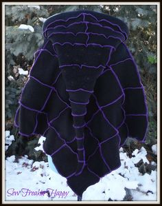Black hooded poncho and matching arm warmers serged with purple thread. made from recycled wool sweaters