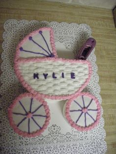 """Cake for niece's baby shower. 10"""" cake with section cut out for handle and 2- 6"""" cakes for wheels.  The handle is made from diaper pin candy mold stacked and """"glued"""" together with icing. The lettering is fondant/gumpaste cut with small alphabet cookie cutters."""
