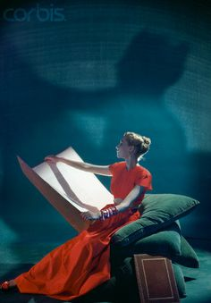 Model Reading Folio in Orange Top and Skirt from Adele Simpson by Cecil Beaton